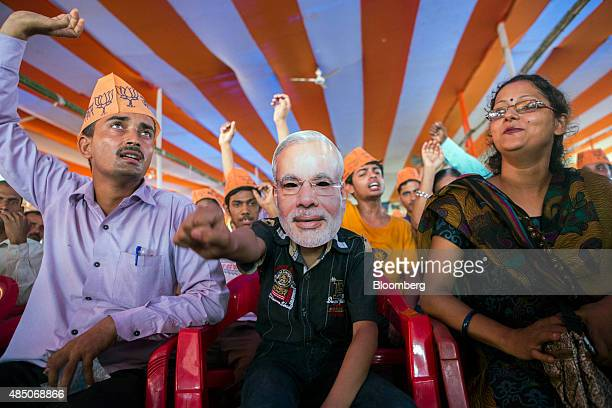 A supporter of the Bharatiya Janata Party wears a mask of Indian Prime Minister Narendra Modi during a rally in Muzaffarpur Bihar India on Saturday...