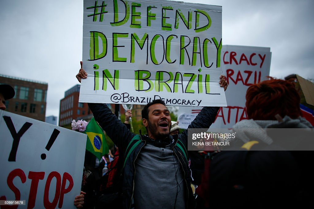A supporter of the Brazilian president Dilma Rousseff, shouts slogans while participating in a May Day rally on May 1, 2016 in New York. Thousands of people attended May Day rallies organized by labor unions in cities across Latin America's biggest country, with Rousseff telling a crowd in the financial powerhouse Sao Paulo that she would 'fight to the end.' / AFP / KENA