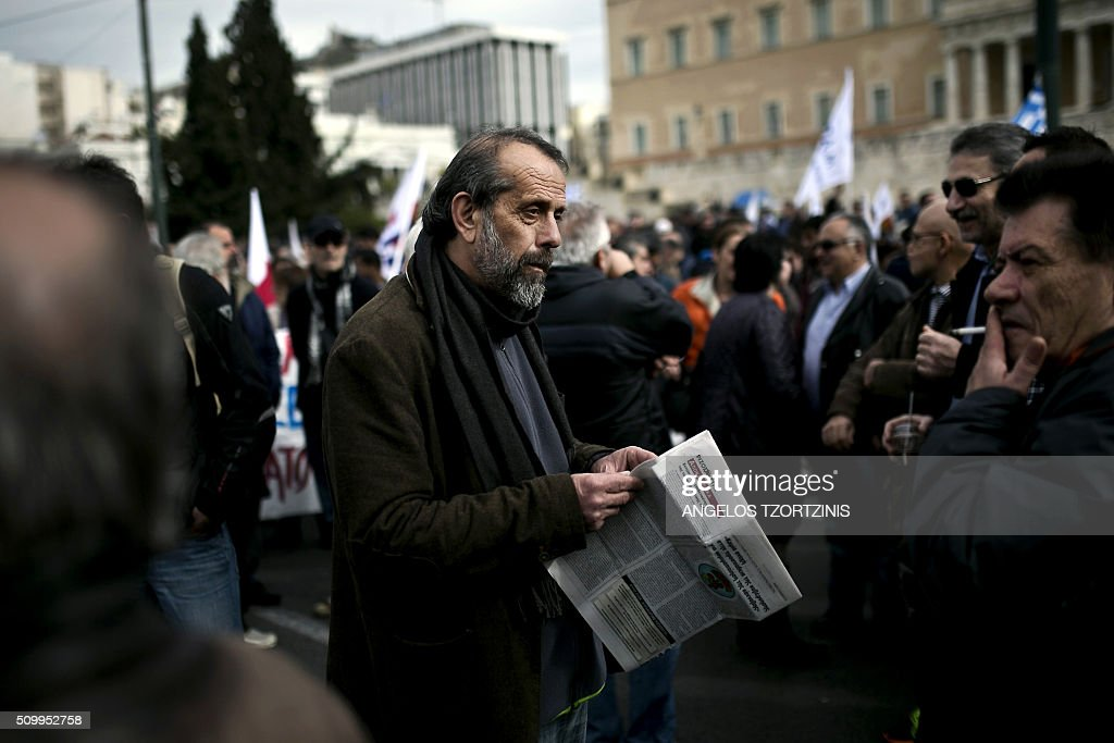 A supporter of the Communist-affiliated trade union PAME reads a newspaper during a protest against pension reform and tax issues, on February 13, 2016 in Athens. Thousands of protesters, especially Supporters of the Communist-affiliated trade union PAME and farmers have again demonstrated on February 13 in Syntagma Square in Athens against a controversial project of pension reform. / AFP / ANGELOS TZORTZINIS