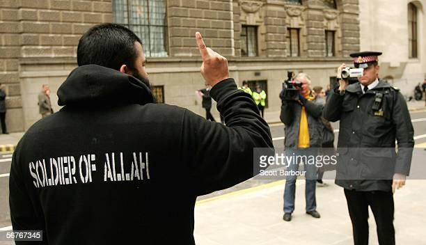 A supporter of the controversial Muslim cleric Abu Hamza alMasri is filmed by a British police officer as he protests outside of the Old Bailey...
