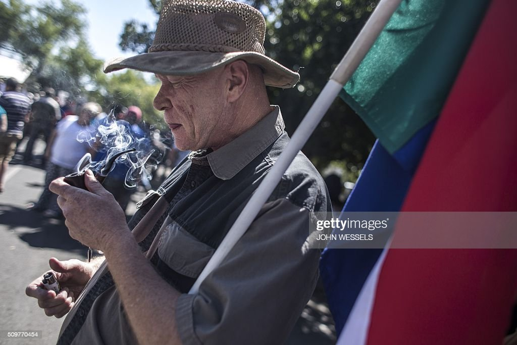A supporter of the four men accused of murdering two farm workers stand outside the Magistrates Court in Parys, Freestate, on February 12, 2016, flying the 'Four Colour' flag of the Old Republic Of The Transvaal. / AFP / JOHN WESSELS