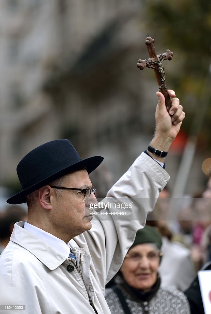 A supporter of the fundamentalist christian group Civitas Institute waves a crucifix as he takes part in a demonstration on October 20, 2013 in Paris, to protest against 'the antichristianism and anti-family policy'.