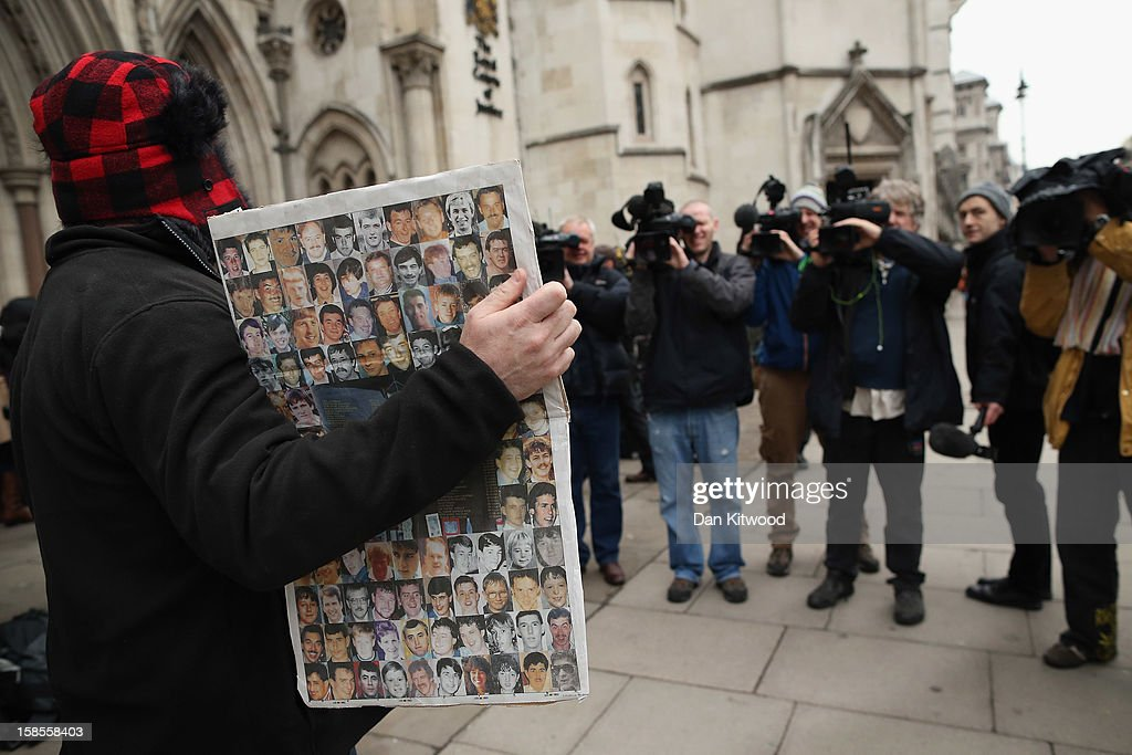 A supporter of the Hillsborough Disaster Support Group holds a copy of a newspaper displaying images of the 96 football fans who lost their lives in the disaster for members of the media outside the High Court on December 19, 2012 in London, England. An application presented by the Attorney General, Dominic Grieve to Lord Chief Justice, Lord Judge has resulted in the quashing of the original accidental death verdict and an order for fresh inquests. The Hillsborough disaster occurred during the FA Cup semi-final tie between Liverpool and Nottingham Forest football clubs in April 1989 at the Hillsborough Stadium in Sheffield, which resulted in the deaths of 96 football fans.