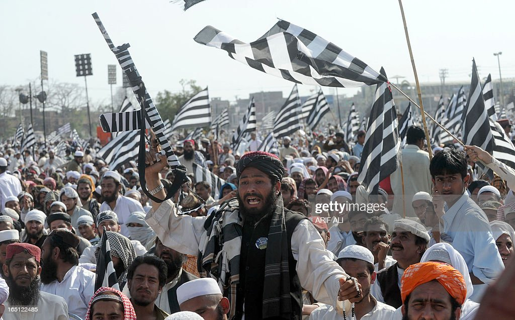 A supporter of the Islamist party Jamiat Ulema-e-Islam Fazl (JUI-F) waves a false gun at an election rally in Lahore on March 31, 2013. Pakistan's political parties organised huge rallies but campaigning for historic general elections in May was marred by a bomb attack which killed two people in the country's northwest. AFP PHOTO/Arif ALI