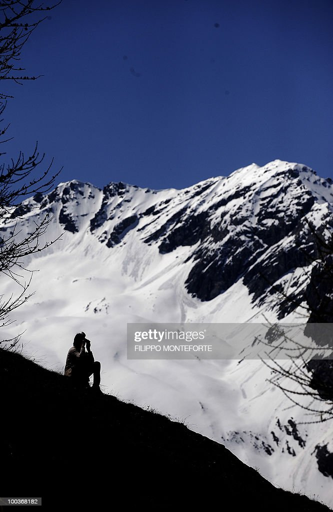 A supporter of the Italian soccer team follows the training session with binoculars from a hill top in Sestriere on May 24, 2010. The italian team is retreating in the mountains of Sestriere before the FIFA World Cup 2010 in South Africa. AFP PHOTO / Filippo MONTEFORTE