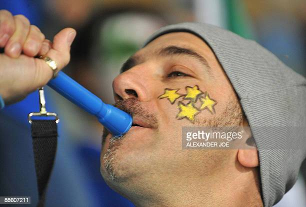 A supporter of the Italian team displaying four stars on his cheek Italy's four trophies in a World Cup plays the vuvuzela in the stands before the...