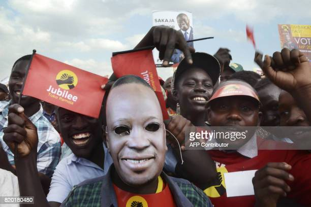 A supporter of the Jubilee Party of Kenya wearing a mask of Kenyan President Uhuru Kenyatta poses with others attending a campaign rally in Nairobi...