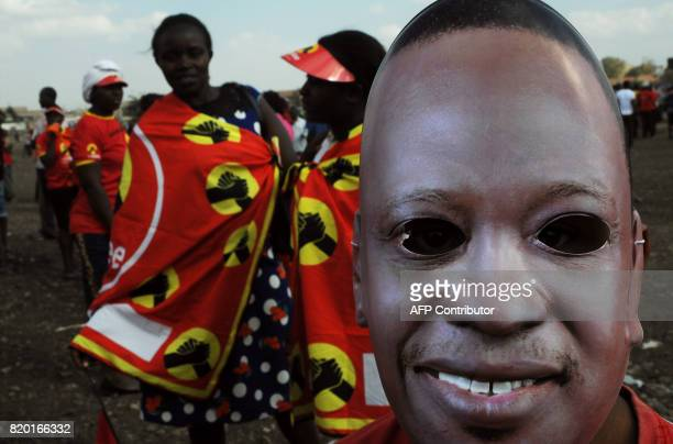 A supporter of the Jubilee Party of Kenya wears a mask of Kenyan President Uhuru Kenyatta as he attends a campaign rally in Nairobi on July 21 2017...