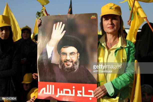 A supporter of the Lebanese Shiite movement Hezbollah holds a poster bearing a portrait of Hassan Nasrallah as she attends on August 31 2017 a rally...