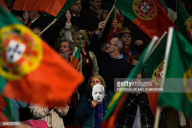 A supporter of the leftwing candidate for Portugal's presidency Antonio Sampaio da Novoa holds a mask with the candidate's face during the campaign...