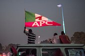 A supporter of the main Nigerian opposition All Progressive Congress party holds a APC flag during a rally in Kaduna on January 19 2015 The head of...
