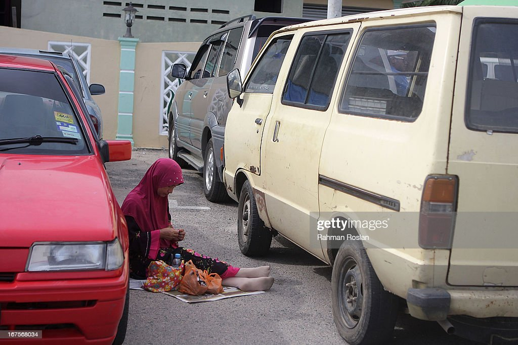 A supporter of the Malaysian Pan Islamic Party sits between a car and a van while istening to the party's President, Hadi Awang's weekly friday sermon on April 26, 2013 in Rusila, Malaysia. Malaysia's 13th general election will be held on May 5.
