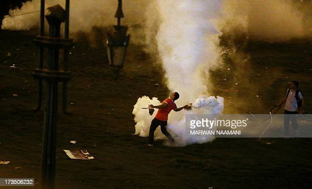 A supporter of the Muslim Brotherhood and Egypt's ousted President Mohamed Morsi returns tear gas canister shot by riot police on July 16 2013 near...