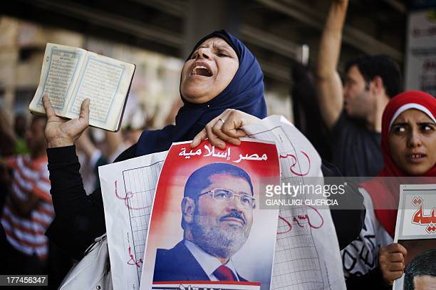 A supporter of the Muslim Brotherhood and Egypt's toppled president Mohamed Morsi shout slogans as she holds a Koran Islam's holy book during a...