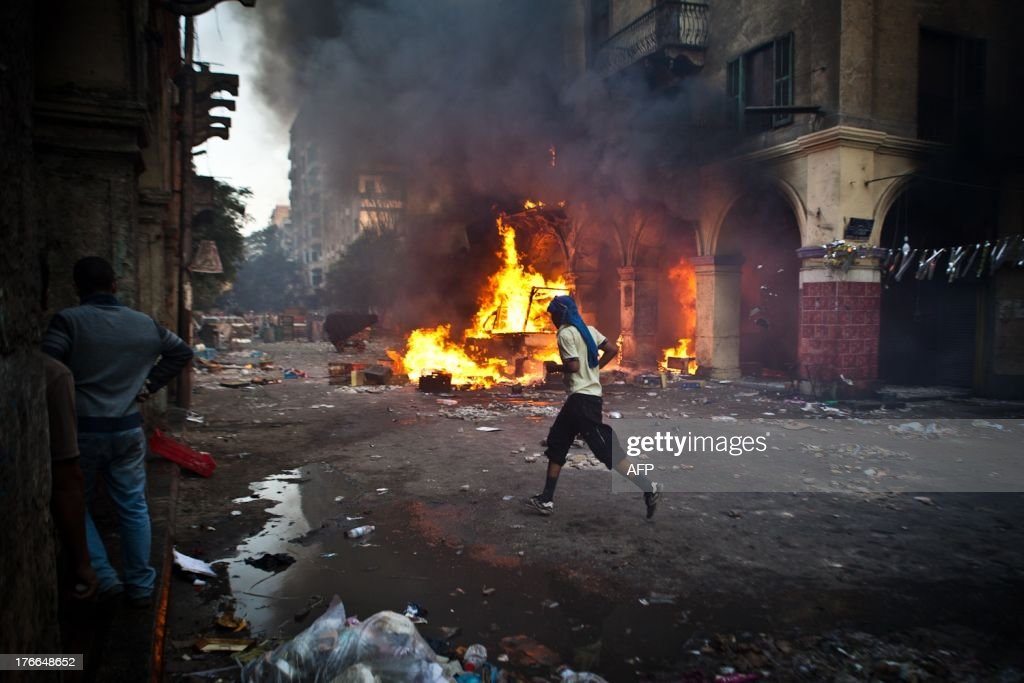 A supporter of the Muslim Brotherhood and of ousted president Mohamed Morsi runs past a burning vehicle during clashes with security officers close...