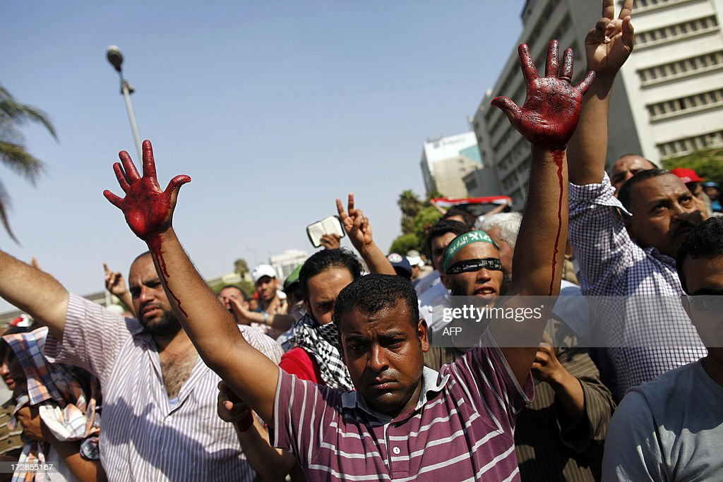 A supporter of the Muslim Brotherhood and ousted Egyptian president Mohamed Morsi raises his hands covered in the blood of victims who were shot during a gun battle outside the Cairo headquarters of the Republican Guard on July 5, 2013. At least three supporters of Morsi were killed and many others were wounded as they gathered for a protest, an AFP correspondent said. Shooting could be heard coming from both the Republican Guard and the ranks of the protesters.