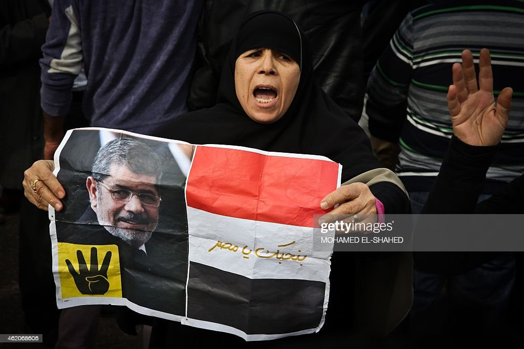 A supporter of the Muslim Brotherhood movement holds a placard showing ousted president <a gi-track='captionPersonalityLinkClicked' href=/galleries/search?phrase=Mohamed+Morsi&family=editorial&specificpeople=7484676 ng-click='$event.stopPropagation()'>Mohamed Morsi</a> during a demonstration on January 24, 2015 in the Cairo district of Heliopolis, ahead of the 4th anniversary of the outbreak of an 18-day uprising that drove former president Hosni Mubarak from power 2011. Morsi's backers regularly attempt anti-government protests that often end in violence. SHAHED