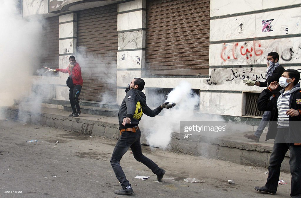 A supporter of the Muslim Brotherhood throws a tear gas cannister during clashes with riot police following a protest in Cairo on December 20, 2013. Supporters of Egypt's former president Mohamed Morsi hold almost daily protests and organise larger rallies on Fridays, despite a crackdown that has killed more than 1,000 people in clashes and imprisoned thousands more since his overthrow by the military.