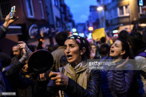 TOPSHOT A supporter of the 'No' hits with a spoon the back of a pan as she takes part in a gather at the Besiktas district in Istanbul on April 17...
