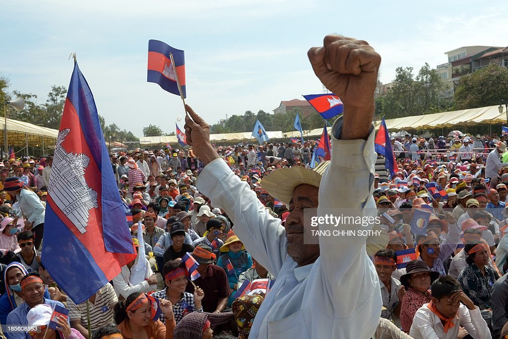 A supporter of the opposition Cambodia National Rescue Party (CNRP) raises his hands during a demonstration at Democracy Park in Phnom Penh on October 23, 2013. Thousands of Cambodia's opposition supporters staged a demonstration amid high security on October 23, over fiercely disputed elections that extended strongman Prime Minister Hun Sen's nearly three-decade rule, following bloody protests last month.