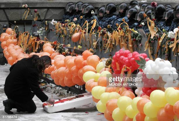 A supporter of the opposition leader Viktor Yushchenko lights a candle infront of a line of riot policemen on guard outside the Presidential office...