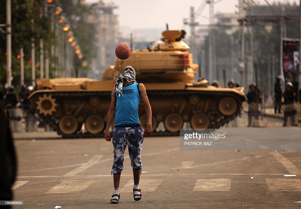 A supporter of the opposition to Egyptian President Mohamed Morsi plays football next to a Republican Guard tank deployed outside the presidential palace in Cairo on December 14, 2012. Egypt's 51 million voters are being called to vote over the next two weekends in a referendum on a draft constitution backed by Islamists, including Morsi, but denounced by the secular opposition.