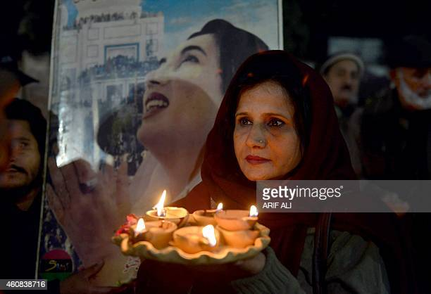 A supporter of the Pakistan Peoples Party holds oil lamps during a rally in Lahore on December 26 2014 to commemorate the seventh death anniversary...