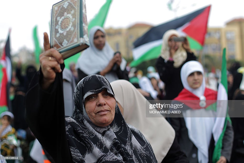 A supporter of the Palestinian Islamic group Hamas shows a Koran, Islam's holy book, during a festival of the International Association of Muslim Scholars head by Muslim cleric Yusuf al-Qaradawi on May 9, 2013 in Gaza City. Al-Qaradawi arrived on May 8, 2013 for his first visit to Gaza Strip with a delegation of Muslim scholars and warned that nobody was allowed to cede 'any part of Palestine'. AFP PHOTO /MOHAMMED ABED