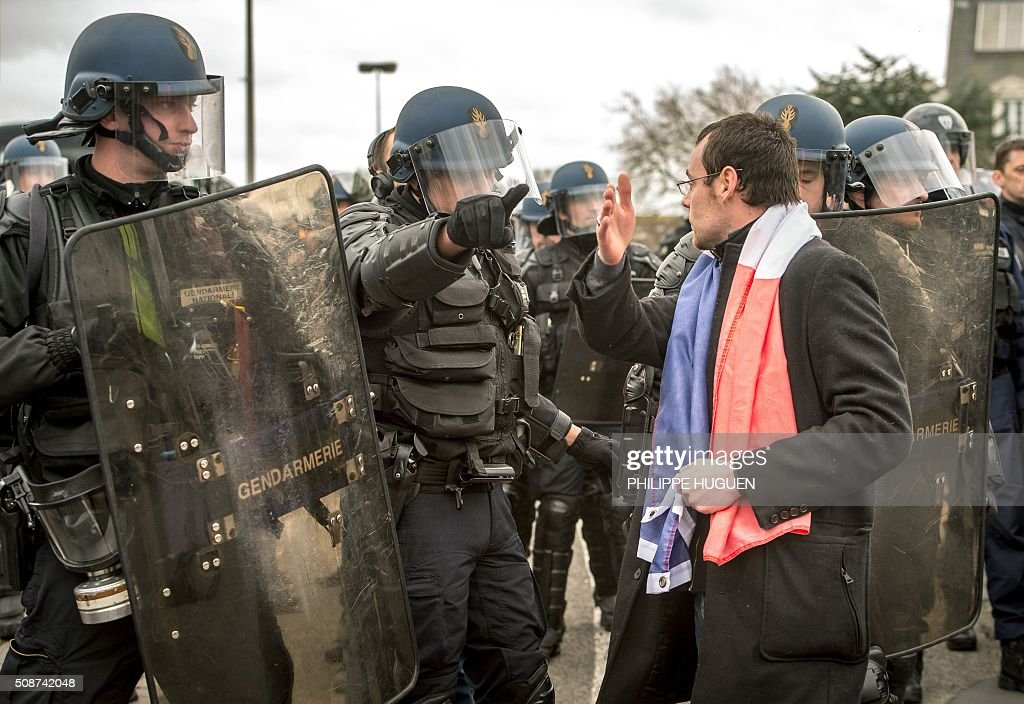 A supporter of the Pegida movement (Patriotic Europeans Against the Islamisation of the Occident) confronts policemen during a demonstration in Calais, northern France on February 6, 2016. Anti-migrant protesters in the French port city of Calais clashed with police as they defied a ban and rallied in support of a Europe-wide initiative by the Islamophobic Pegida movement. / AFP / PHILIPPE HUGUEN