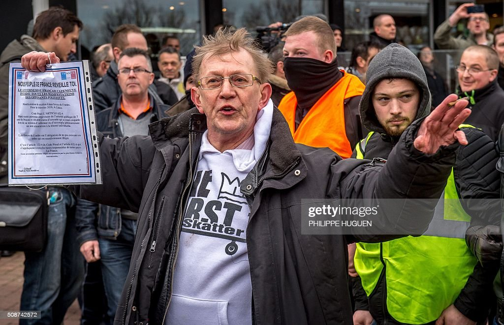 A supporter of the Pegida movement (Patriotic Europeans Against the Islamisation of the Occident) holds a document reading 'Franch people wake up, the government bans demonstrations by the opposition' during a demonstration in Calais, northern France on February 6, 2016. Anti-migrant protesters in the French port city of Calais clashed with police as they defied a ban and rallied in support of a Europe-wide initiative by the Islamophobic Pegida movement. / AFP / PHILIPPE HUGUEN