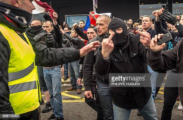 A supporter of the Pegida movement wearing a balaclava gives the finger during a banned demonstration in Calais northern France on February 6 2016...