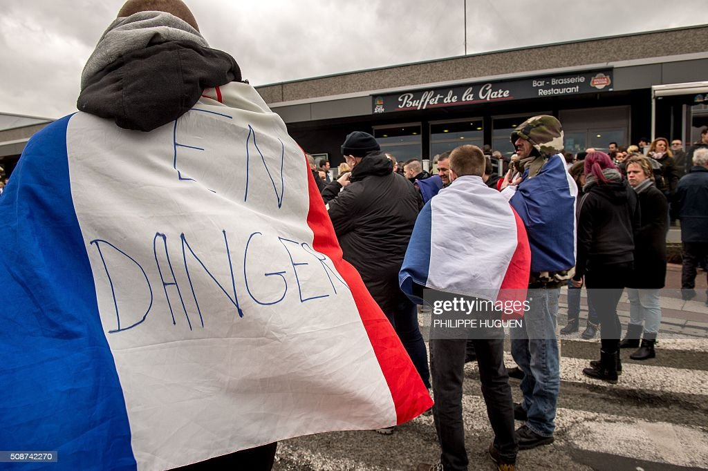 A supporter of the Pegida movement (Patriotic Europeans Against the Islamisation of the Occident) wears a French flag reading 'In danger' during a demonstration in Calais, northern France on February 6, 2016. Anti-migrant protesters in the French port city of Calais clashed with police as they defied a ban and rallied in support of a Europe-wide initiative by the Islamophobic Pegida movement. / AFP / PHILIPPE HUGUEN
