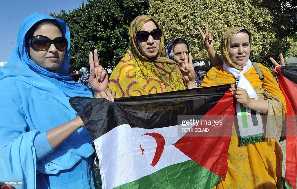 Supporter of the Polisario Front separatist movement wave the party's flag as they flash the sign for victory at the opening of the World Social Forum (WSF) on March 26, 2013 in Tunis. More than two years after the Jasmine revolution, tens of thousands of people are expected for the WSF, dubbed the forum of 'dignity', a watchword of the Tunisian uprising that inspired revolts across the Arab world.