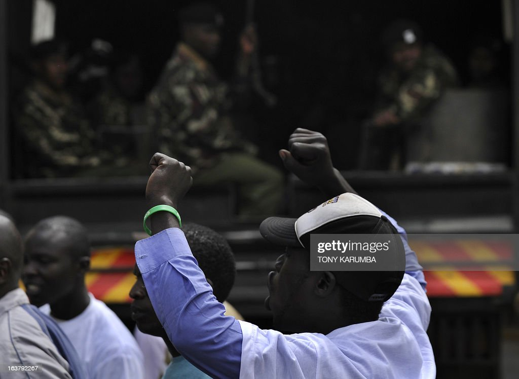 A supporter of the Raila Odinga led CORD alliance raises his hands as he shouts in front of the police on March 16, 2013, outside Kenya's supreme court building, who was injured by a tear gas canister fired by police at youth who had gathred to express support for a petition challenging the outcome of Kenya's general election. Kenya's outgoing Prime Minister Raila Odinga, who was narrowly defeated in presidential polls by Uhuru Kenyatta, filed a formal challenge Saturday against the result. Officials from Odinga's Coalition for Reform and Democracy (CORD) filed the suit at the Supreme Court after Odinga spoke to supporters and journalists in front of his offices. AFP PHOTO/Tony KARUMBA