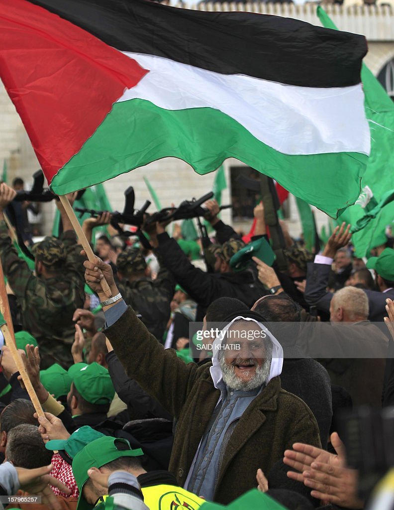 A supporter of the ruling Hamas movement holds up the palestinian flag during a rally to mark the 25th anniversary of the founding of the Islamist movement, in Gaza City on December 8, 2012. Hamas leader in exile Khaled Meshaal made his first visit to Gaza, timed to coincide with the 25th anniversary of the Islamist movement's founding.