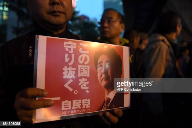 A supporter of the ruling Liberal Democratic Party displays a poster while waiting for Japan's Prime Minister Shinzo Abe to arrive for his last...