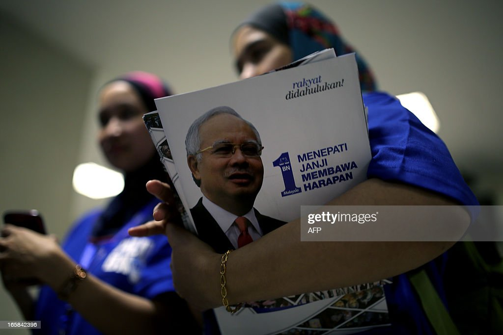 A supporter of the ruling National Front coalition, or Barisan Nasional, carries manifestos after the launching by Malaysia's Prime Minister Najib Razak at a stadium in Bukit Jalil, a suburb of Kuala Lumpur, on April 6, 2013. Malaysia's premier Najib Razak unveiled a manifesto on Saturday pledging bigger cash handouts, millions of new jobs and lower taxes and crime, as he seeks his first mandate in looming national polls. AFP PHOTO / MOHD RASFAN