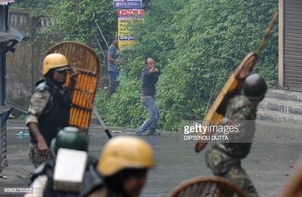 TOPSHOT A supporter of the separatist Gorkha Janmukti Morcha group fires a slingshot during clashes with Indian security forces in Darjeeling on June...