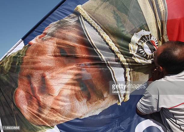 A supporter of the Serbian Radical Party kisses a flag that depicts Ratko Mladic former Chief of Staff of the Bosnian Serb army and currently on...
