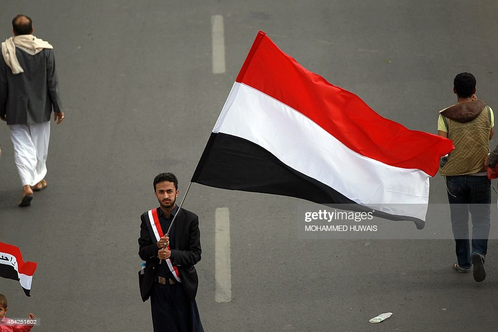 A Supporter of the Shiite Huthi movement holds his national flag as he takes part in an anti-government protest on August 27, 2014 in the Yemeni capital Sanaa. Yemeni President Abdrabuh Mansur Hadi urged Shiite rebel leader Abdulmalik al-Huthi on August 26 to withdraw his militant followers from the capital following the failure of negotiations on their demands.