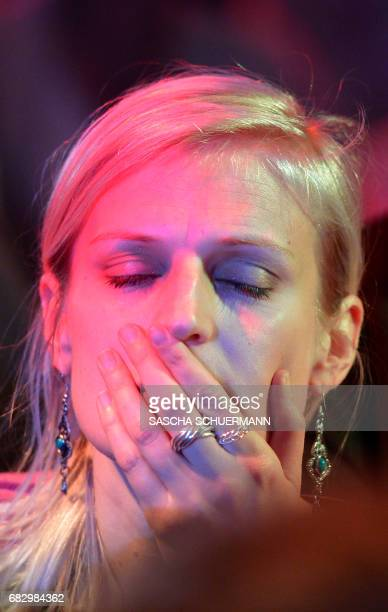A supporter of the social democratic SPD party reacts as preliminary results of regional elections in the western German state of North...