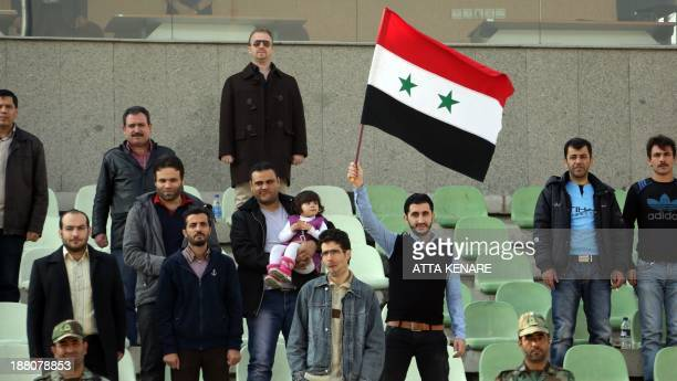 A supporter of the Syria national football team waves a flag during their 2015 Asian Cup group A qualifying football match Syria versus Singapore at...