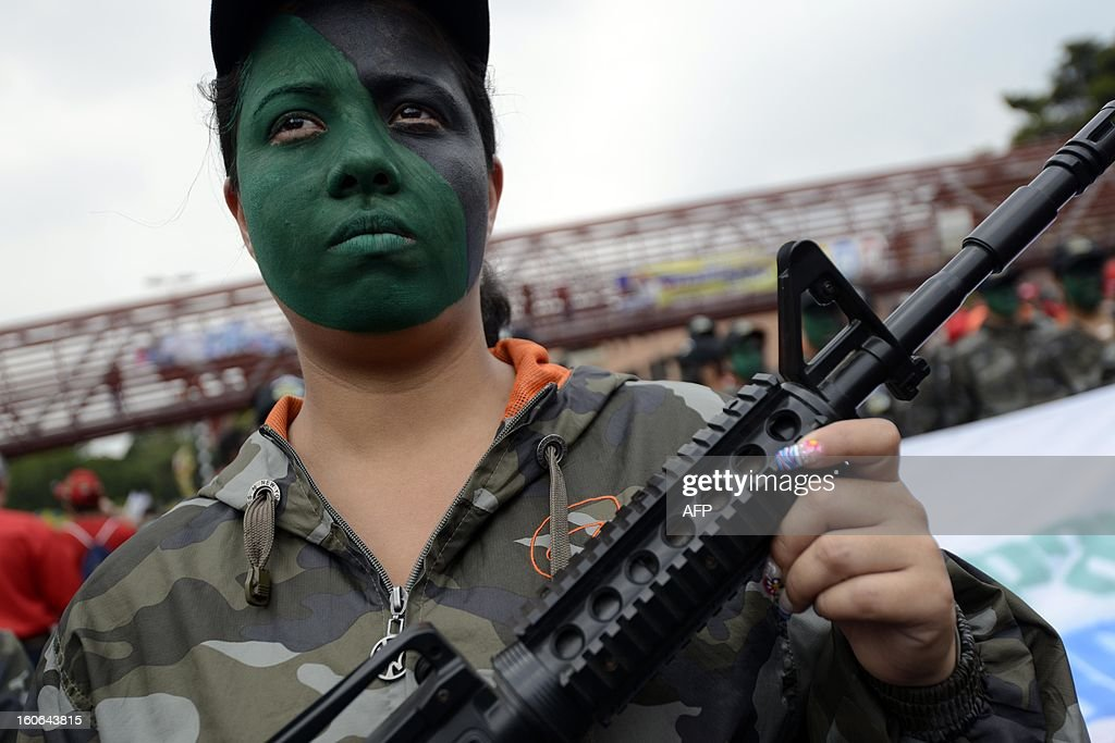 A supporter of the Venezuelan President Hugo Chavez with a fake gun takes to the streets to conmemorate the 1992 failed coup led by Chavez, who was an army lieutenant colonel, against then president Carlos Andres Perez, in Caracas, on February 4, 2013. Ailing President Hugo Chavez, who had cancer surgery in December, is doing much better and recovering, Cuban leader Fidel Castro said in remarks published Monday. AFP PHOTO/Leo RAMIREZ