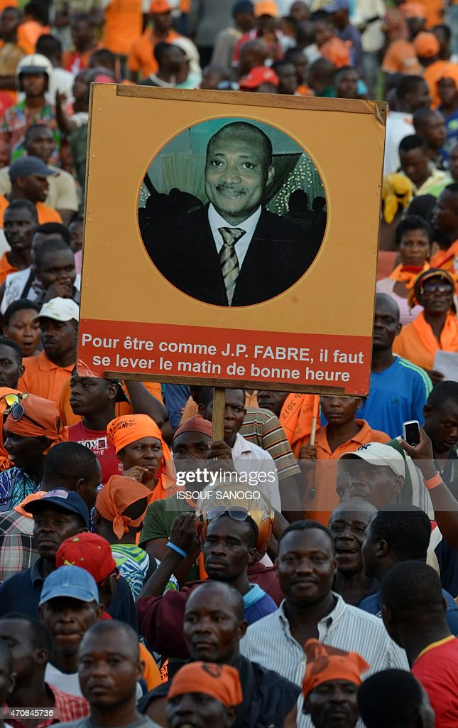 A supporter of Togo's opposition leader and Alliance for National change candidate for presidential election <a gi-track='captionPersonalityLinkClicked' href=/galleries/search?phrase=Jean-Pierre+Fabre&family=editorial&specificpeople=2329955 ng-click='$event.stopPropagation()'>Jean-Pierre Fabre</a>, holds a campaign banner during a presidential campaign meeting on April 23, 2015 in Lome.