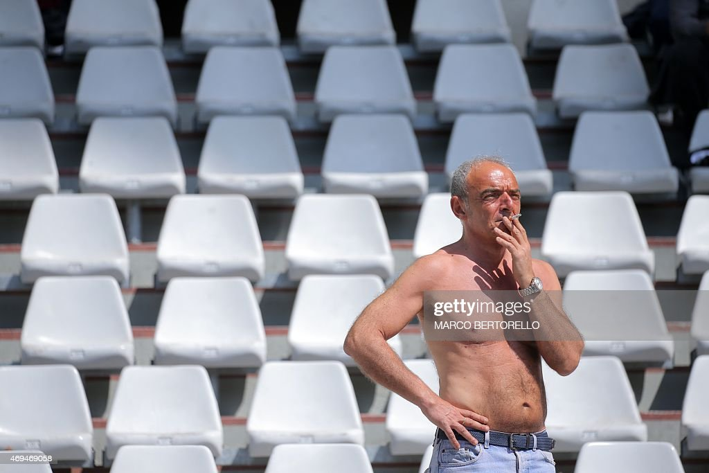 A supporter of Torino smokes a cigarette in the stands during the Italian Serie A football match Torino Vs AS Roma on April 12 2015 at the 'Olympic...