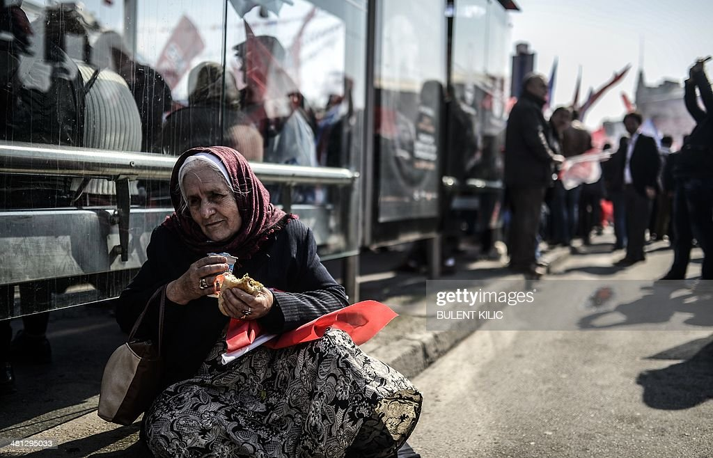 A supporter of Turkey's main opposition Republican People's Party (CHP) eats her lunch during an election rally at Kadikoy in Istanbul on March 29, 2014. Turkey gears up for local elections on March 30 ahead of a presidential vote in six months and parliamentary polls next year. Turkey's Premier Recep Tayyip Erdogan and his Islamic-leaning party, after over a decade in power, face the first electoral test following months of political turmoil, with mass street protests and a corruption scandal spread via Twitter, Facebook and YouTube. Amid an atmosphere of distrust ahead of tomorow's election with over 50 million eligible voters, the CHP and tens of thousands of citizen volunteers plan to monitor the ballot count.