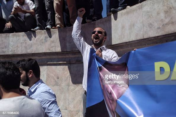 A supporter of Turkish President Recep Tayyip Erdogan holds up a banner during a rally in Fatih district on July 19 2016 in Istanbul Turkey Clean up...
