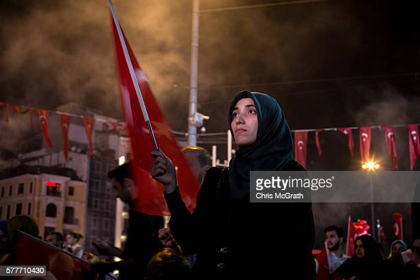 A supporter of Turkish President Recep Tayyip Erdogan watches on during a rally in Taksim Square on July 19 2016 in Istanbul Turkey Clean up...
