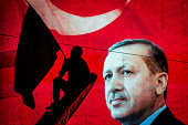A supporter of Turkish President Recep Tayyip Erdogan waves a flag against an electronic billboard during a rally in Kizilay Square on July 18 2016...