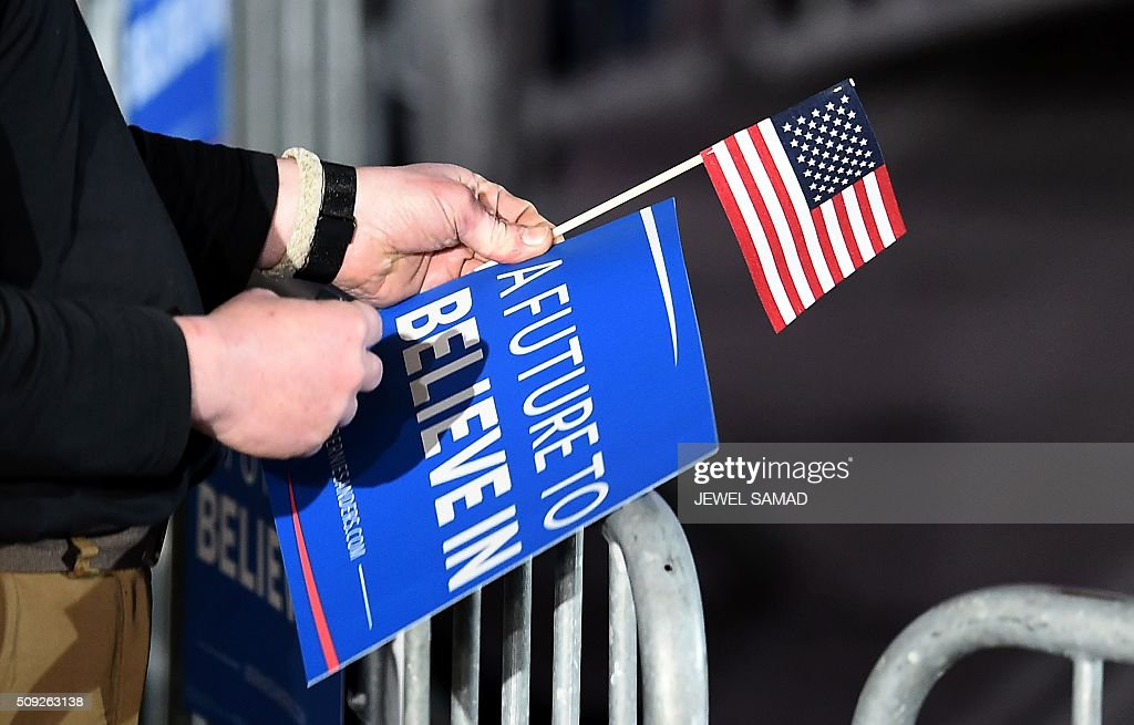 A supporter of US Democratic presidential candidate Bernie Sanders holds a campaign poster and a US flag as he arrives for primary night rally in Concord, New Hampshire, on February 9, 2016. / AFP / Jewel Samad